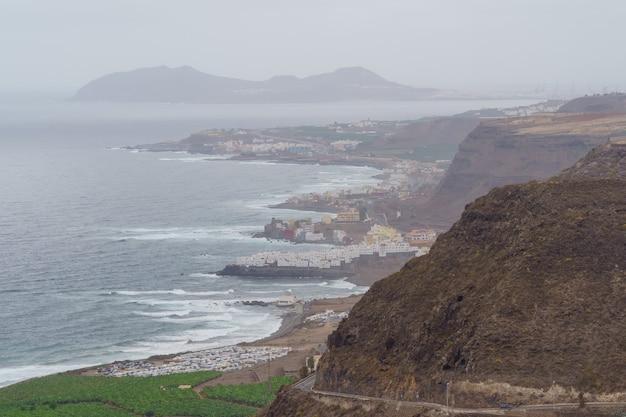 Luchtfoto van de bergen van het eiland gran canaria en de kust naast de zee met wolken en mist op de achtergrond. spanje, europa,