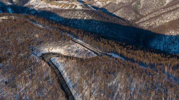 Luchtfoto van de bossen van de rivier en de taiga en de weg in het abstracte winterlandschap van de lente van de noordelijke natuur met drone