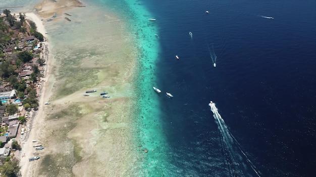Luchtfoto van de boten die op de blauwe oceaan aan de kust varen