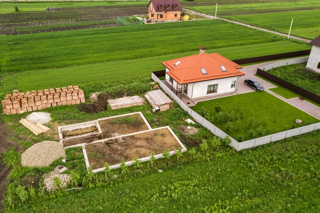 Luchtfoto van de bouwplaats voor toekomstige bakstenen huis, betonnen funderingsvloer en stapels gele bakstenen voor de bouw.