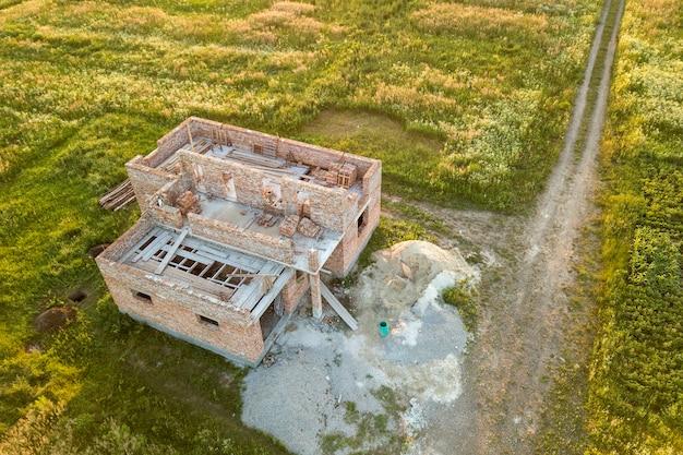 Luchtfoto van de bouwplaats voor toekomstige huis, bakstenen kelderverdieping en stapels baksteen voor constructie.