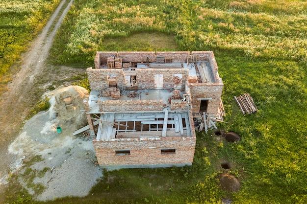 Luchtfoto van de bouwplaats voor toekomstige huis, bakstenen kelderverdieping en stapels bakstenen.