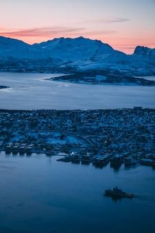 Luchtfoto van de gebouwen en de met sneeuw bedekte bergen die zijn vastgelegd in tromso, noorwegen