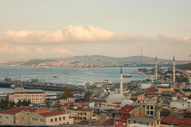 Luchtfoto van de gouden hoorn en de brug van de galata van de daken van huizen en de toren van de moskee. istanbul, turkije