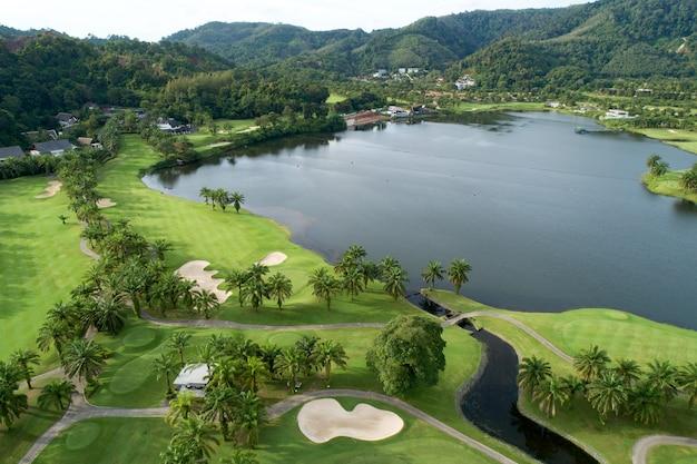 Luchtfoto van de groene golfbaan in thailand prachtig groen gras en bomen op een golfveld met fairway en putting green in het zomerseizoen.