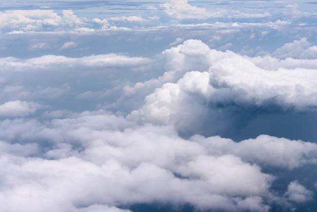Luchtfoto van de grote witte wolken en regenende wolken op blauwe hemel boven de blauwe oceaan