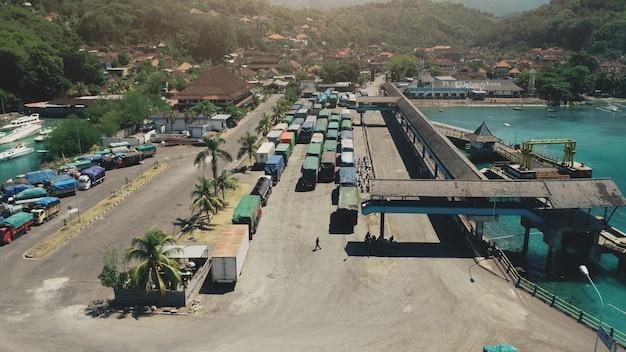 Luchtfoto van de havenhaven van het eiland met veel vrachtwagens klaar om naar het kristal van de veerboot te gaan