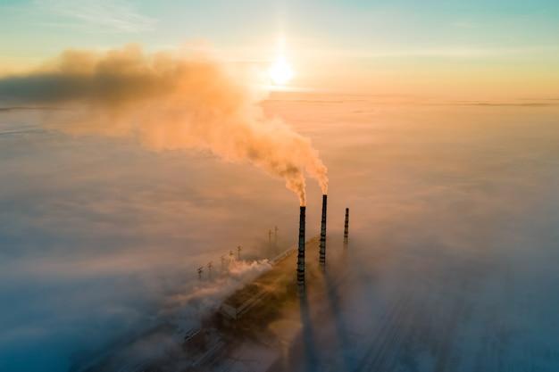 Luchtfoto van de hoge pijpen van de kolencentrale met zwarte rook die de vervuilende atmosfeer omhoog beweegt bij zonsondergang.