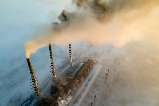Luchtfoto van de hoge pijpen van de kolencentrale met zwarte rook die de vervuilende atmosfeer omhoog beweegt bij zonsopgang.