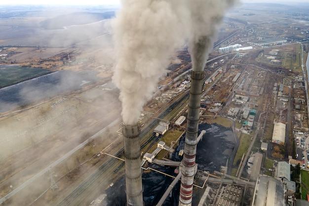 Luchtfoto van de hoge pijpen van de kolencentrale met zwarte rook die de vervuilende atmosfeer omhoog beweegt.
