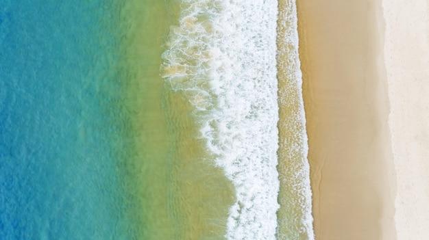 Luchtfoto van de kleurovergang van het oceaanoppervlak met golven die aan de kust van de andaman-oceaan wassen verbazingwekkende top-down natuur landschap zeegezicht uitzicht mooi voor reizen achtergrond en website.