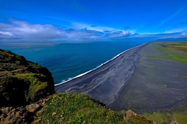 Luchtfoto van de kustlijn in de buurt van de berg onder een blauwe hemel overdag