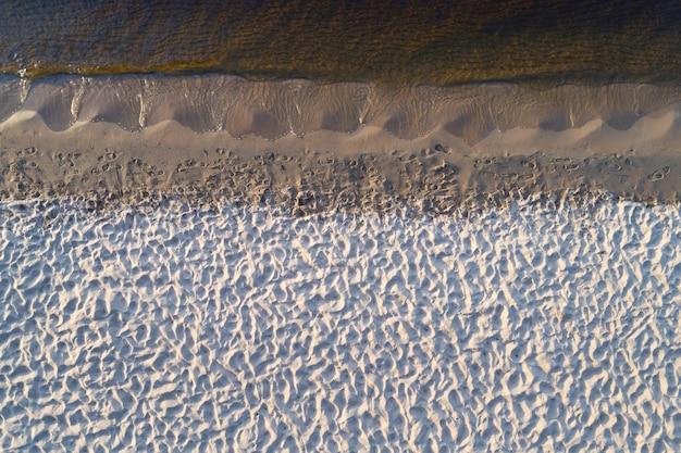 Luchtfoto van de lege oever van het meer met zacht wit zand. rechte branding.
