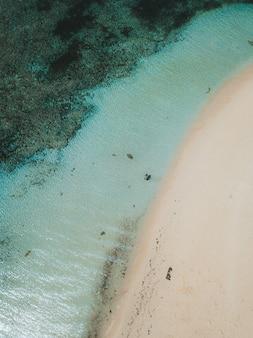 Luchtfoto van de oceaangolven die het zandstrand raken