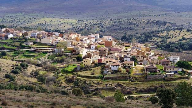 Luchtfoto van de oude stad in de vallei, omringd door bergen en groene planten. paredes buitrago madrid.
