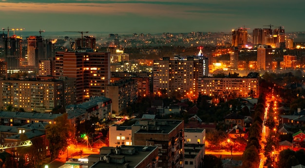 Luchtfoto van de prachtige brandende lichten van een avondstad doordrenkt van mist met hoogbouw en een bouwplaats