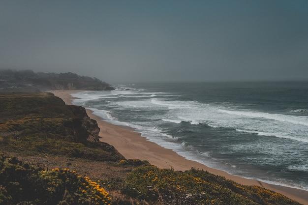 Luchtfoto van de prachtige zand kust van de zee met een donkergrijze hemel