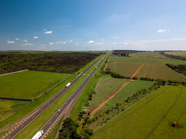 Luchtfoto van de rechte weg langs suikerriet veld in de staat sao paulo, brazilië.