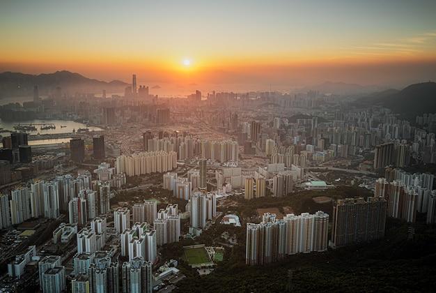 Luchtfoto van de skyline van de stad onder een oranje hemel bij zonsondergang