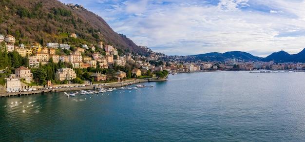 Luchtfoto van de skyline van een kuststad omringd door hoge beboste bergen en een gladde kalme zee