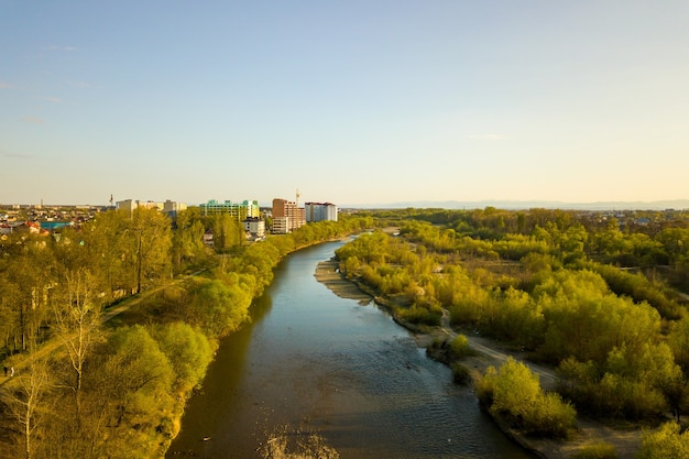 Luchtfoto van de stad ivano-frankivsk, oekraïne met de bystrytsia-rivier en hoge woongebouwen in aanbouw op afstand.