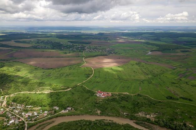 Luchtfoto van de stad of dorp met rijen van gebouwen en bochtige straten tussen groene velden in de zomer. platteland landschap van bovenaf.