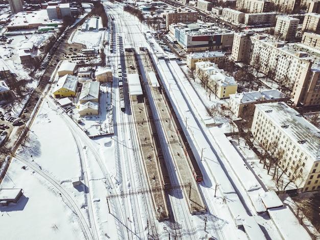 Luchtfoto van de trein op het spoor langs in de stad op een winterse dag
