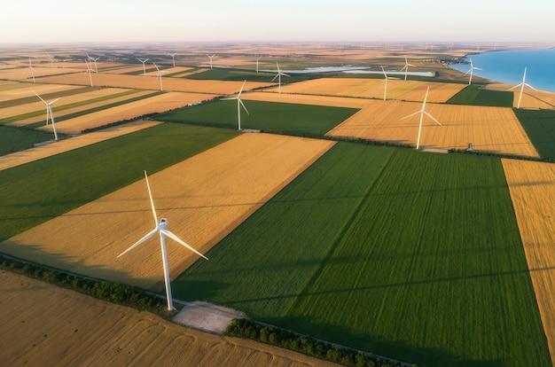 Luchtfoto van de turbines van hernieuwbare windmolens die het teeltgebied voorzien van eco-energie die energie haalt uit de wind die waait op een uitgestrekt gebied van landbouwweiden naast de zee. alternatieve elektriciteit