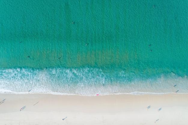 Luchtfoto van de turkooizen kleur van het oceaanoppervlak met golven die aan de kust van de andaman-oceaan wassen verbazingwekkende top-down natuur landschap zeegezicht uitzicht mooi voor reizen achtergrond en website.