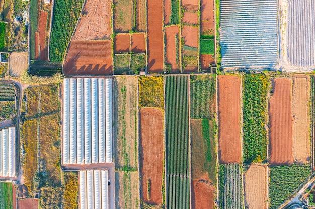 Luchtfoto van de verschillende velden met gewassen en kassen. concept van agro-industrieel complex.