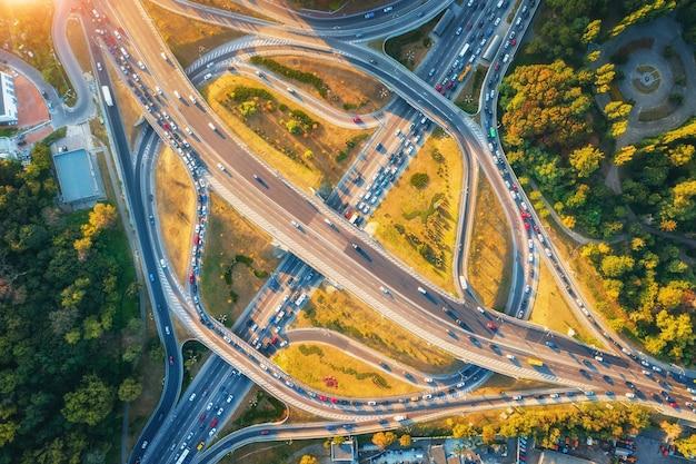 Luchtfoto van de weg in de moderne stad bij zonsondergang in de zomer. bovenaanzicht van verkeer in snelwegknooppunt. landschap met auto's op verhoogde weg, groene bomen. viaduct overstappen. druk kruispunt. spitsuur