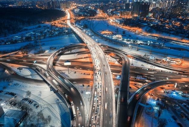 Luchtfoto van de weg in de moderne stad 's nachts in de winter. bovenaanzicht van verkeer in snelweg, gebouwen, verlichting.