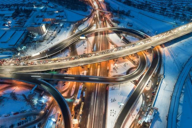 Luchtfoto van de weg in de moderne stad 's nachts in de winter. bovenaanzicht van verkeer in snelwegknooppunt met verlichting.