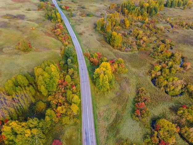 Luchtfoto van de weg met een schilderachtig herfstlandschap. heldere herfstkleuren, drone-opnamen van de schilderachtige herfst. bovenaanzicht