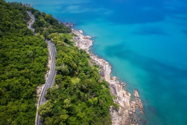 Luchtfoto van de weg tussen coconut palmboom en grote oceaan overdag