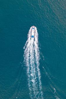 Luchtfoto van de zee met een motorboot die deze oversteekt en een wit spoor achterlaat