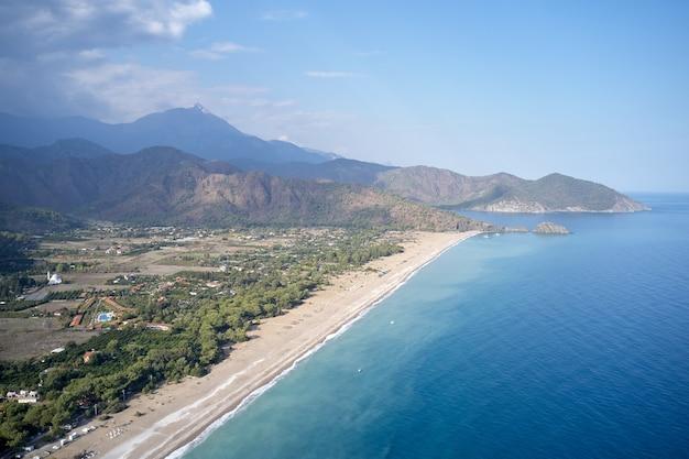 Luchtfoto van de zeekust met bergen op de achtergrond. bovenaanzicht van de kust van badplaats. zomervakantie concept.