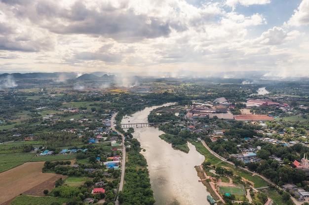 Luchtfoto van dorp aan de kust met rivier en suikerprocesfabriek en rook in plantage