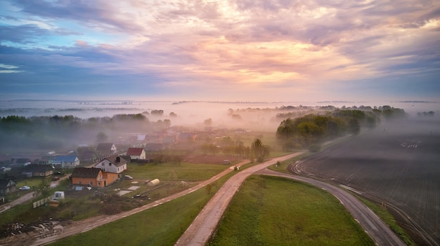 Luchtfoto van dorp, landelijke onverharde weg en bomen bedekt met mist. het vroege mistige panorama van de ochtendzonsopgang. lente zomer velden. regenachtig bewolkt humeurig weer. wit-rusland, regio minsk