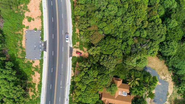 Luchtfoto van drone bovenaanzicht van asfaltweg met groen bos