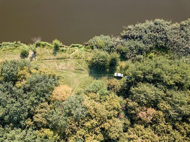Luchtfoto van drone-recreatieplaats aan een oever van de rivier. bovenaanzicht groene bomen, weide en witte auto. bovenaanzicht.