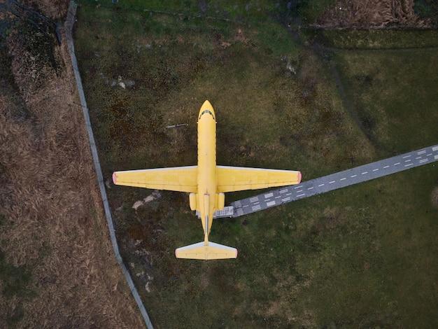 Luchtfoto van drone van een klein oud gele jet passagiersvliegtuig staande in een veld