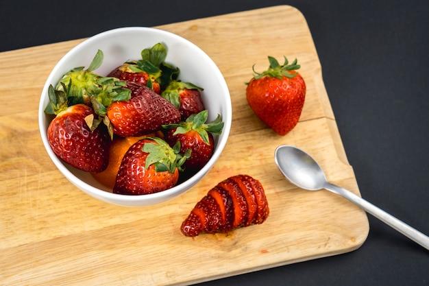Luchtfoto van een aardbei gesneden op een hout en een witte kom met meer aardbeien, recept voor zelfgemaakte aardbeien