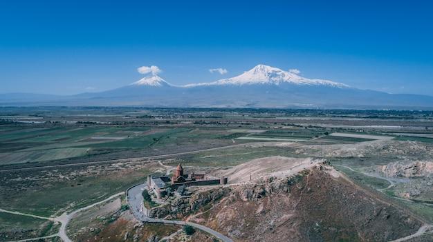 Luchtfoto van een armeense kerk op een heuvel met berg ararat en heldere blauwe hemel