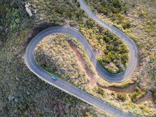 Luchtfoto van een auto die door een spiraalvormige weg rijdt, omringd door bomen op het platteland