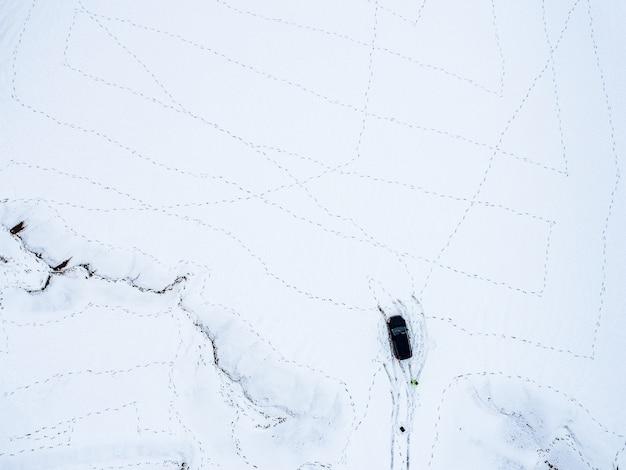 Luchtfoto van een auto geparkeerd op een besneeuwd veld bedekt met voetafdrukken in de winter