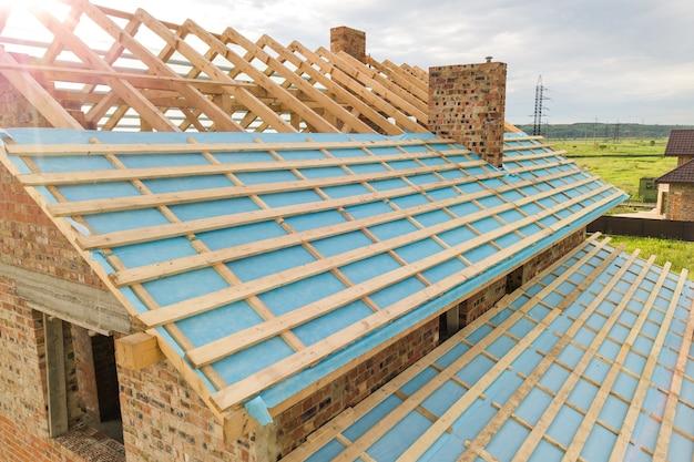 Luchtfoto van een bakstenen huis met houten dakframe in aanbouw.