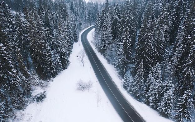 Luchtfoto van een bergweg in het bos van de winter
