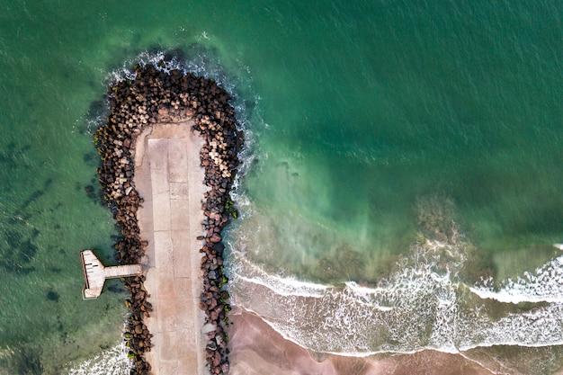 Luchtfoto van een betonnen pier op zee met golfbrekende stenen.