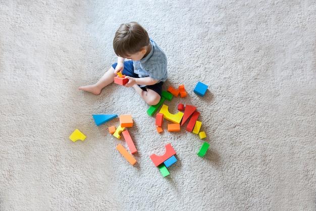 Luchtfoto van een blonde jongen spelen met educatieve blok houten spelletjes voor kinderen.